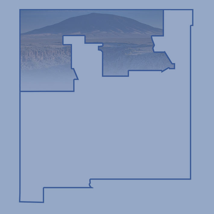 Northern New Mexico map with a photo of Taos Gorge faded in the area